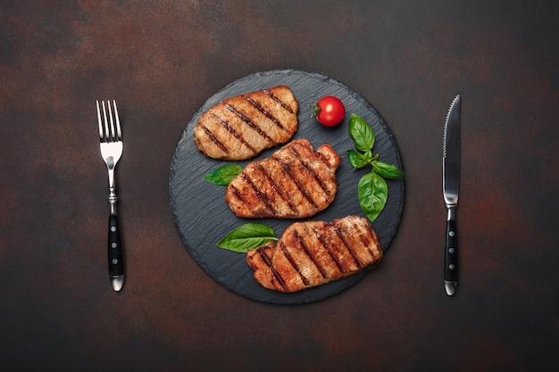 Steaks de porc grillés au basilic, tomates, couteau et fourchette sur pierre noire et fond rouillé brun Photo Premium