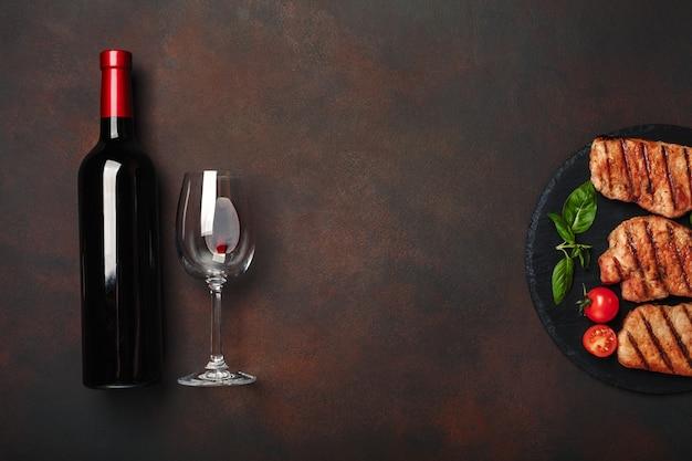 Steaks de porc grillés sur pierre avec bouteille de vin, verre à vin, couteau et fourchette sur fond rouillé Photo Premium