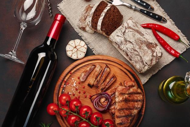 Steaks de porc grillés en tranches avec bouteille de vin, verre à vin, tire-bouchon, couteau, fourchette, pain noir, tomates cerises, ail, oignon et romarin sur fond rouillé Photo Premium