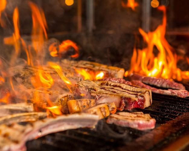 Steaks de viande trop cuit dans les flammes sur le gril Photo gratuit