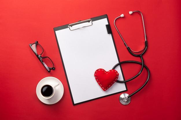 Stéthoscope au bureau du docteur avec tablette, coeur et tasse à café, vue de dessus Photo Premium