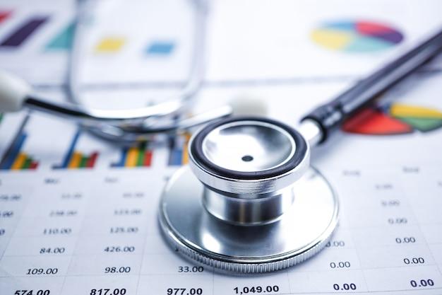 Stéthoscope et billets en dollars américains sur un papier graphique ou graphique. Photo Premium