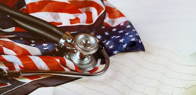 Stéthoscope et cardiogramme sur table drapeau américain Photo Premium