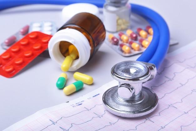 Stéthoscope close-up allongé sur une ordonnance rx avec des pilules assorties. vie saine ou concept d'assurance. Photo Premium
