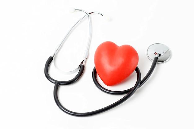 Stéthoscope et coeur rouge bouchent sur fond blanc Photo Premium