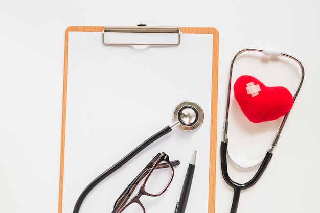 Stéthoscope avec coeur rouge en peluche avec bandage sur presse-papiers Photo gratuit