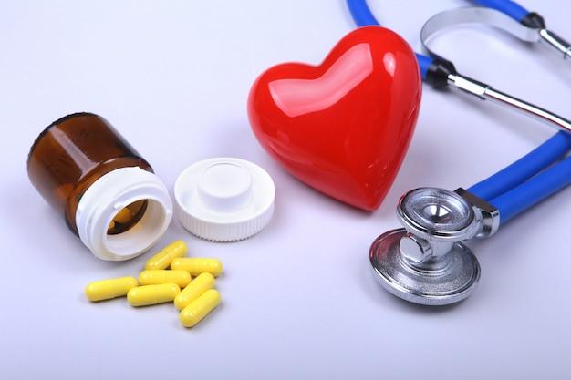 Stéthoscope, coeur rouge et pilules assorties. Photo Premium