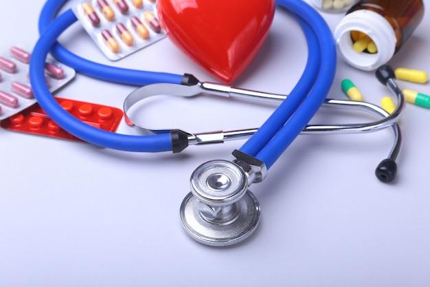 Stéthoscope et coeur rouge, pilules colorées, comprimés, blisters pour la pharmacie et la médecine. Photo Premium