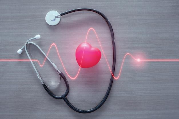 Stéthoscope et coeur rouge avec vague rougeoyante de coeur. Photo Premium