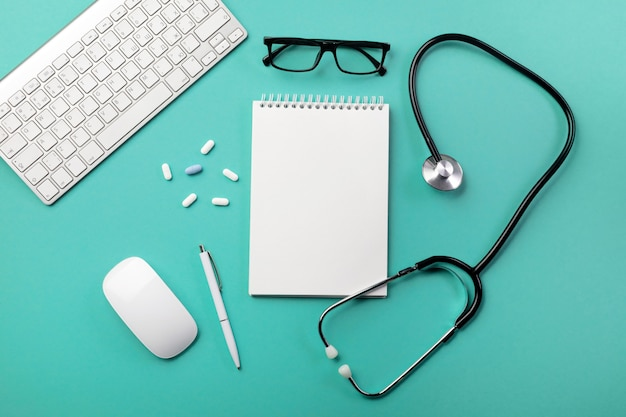 Stéthoscope dans le bureau du médecin avec carnet, stylo, clavier, souris et pilules Photo Premium