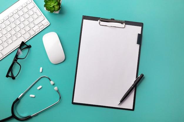Stéthoscope dans le bureau du médecin avec tablette, stylo, clavier, souris et pilules Photo Premium