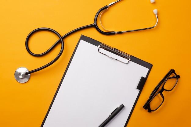 Stéthoscope dans le bureau du médecin avec tablette, stylo et pilules Photo Premium