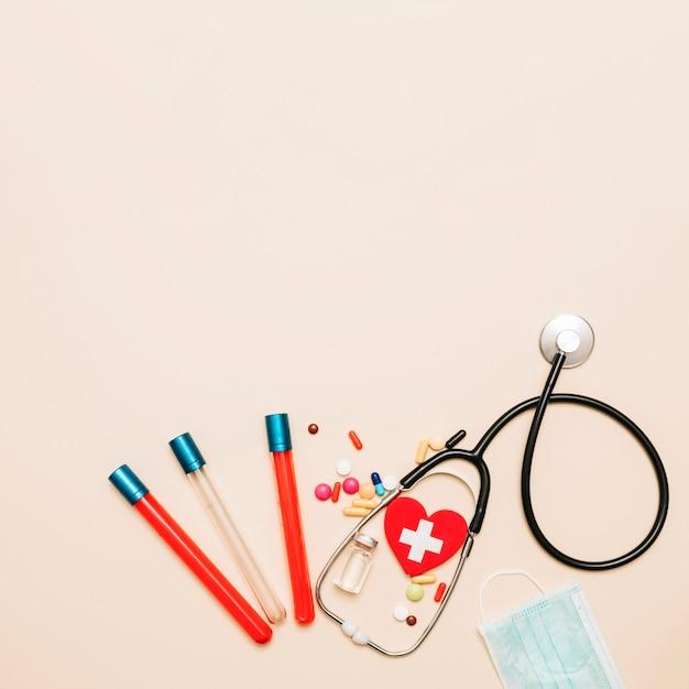 Stéthoscope et échantillons de sang près des médicaments Photo gratuit