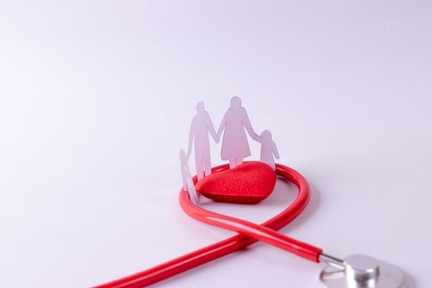 Stéthoscope enroulé autour d'un cœur rouge et d'une figure de famille sur du papier blanc Photo Premium