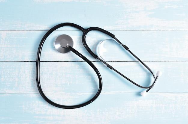 Stéthoscope sur fond en bois pastel blanc. soins de santé mondiaux et concept de la journée mondiale de la santé. Photo Premium