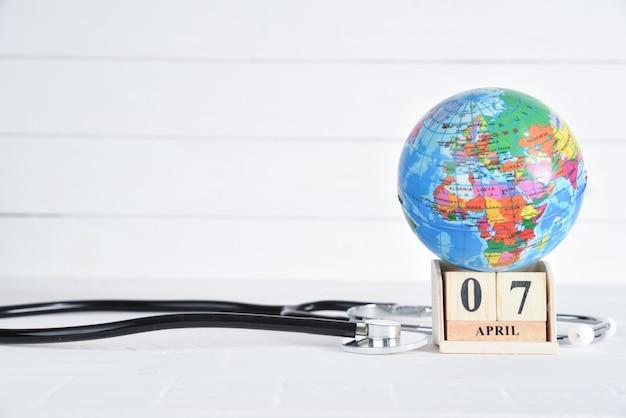 Stéthoscope et globe avec calendrier de bloc de texte du 7 avril sur fond en bois blanc. Photo Premium