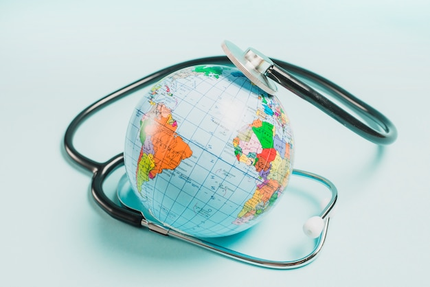 Stéthoscope sur le globe sur fond bleu Photo gratuit