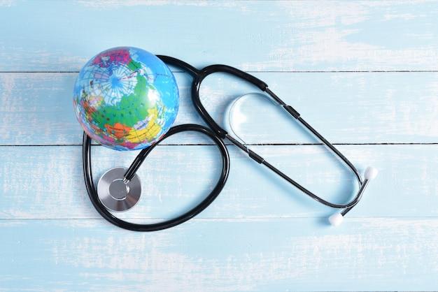 Stéthoscope et globe sur fond en bois pastel bleu et blanc. Photo Premium