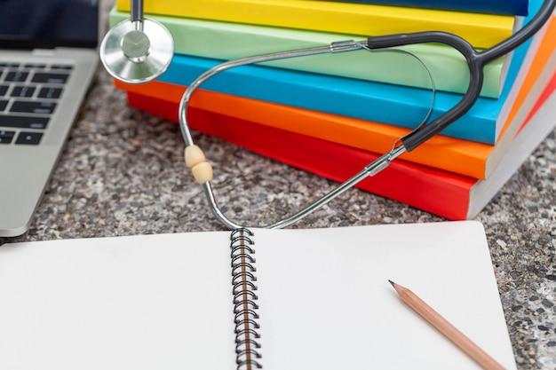 Stéthoscope médical avec le bloc-notes et des livres sur le bureau, concept médical. Photo Premium