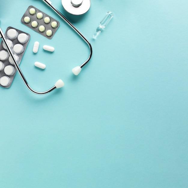 Stéthoscope avec des médicaments emballés sous blister sur fond bleu Photo gratuit