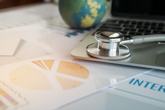 Stéthoscope sur ordinateur avec assurance médicale internationale, formulaires de réclamation de soins de santé Photo Premium