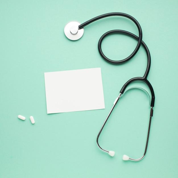 Stéthoscope avec papier blanc et pilules blanches sur fond vert pastel Photo gratuit