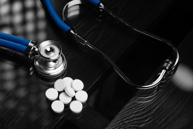 Stéthoscope et pilules sont sur la table noire Photo Premium