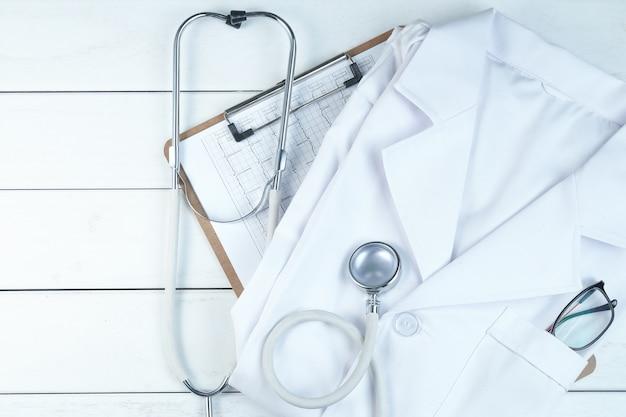 Le Stéthoscope, Le Presse-papiers Et L'uniforme Du Médecin Sur Le Bureau Blanc En Bois Pur Photo gratuit