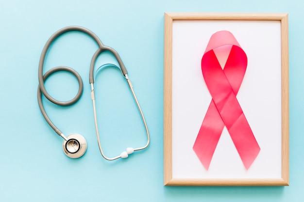 Stéthoscope et ruban rose sur un cadre en bois blanc sur le fond coloré Photo gratuit