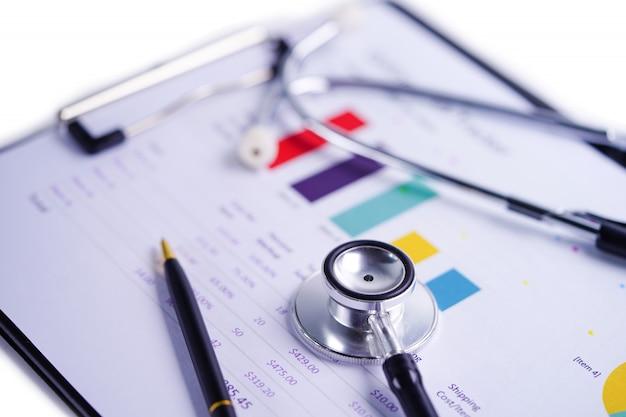 Stéthoscope sur tableaux et graphiques feuille de calcul. Photo Premium
