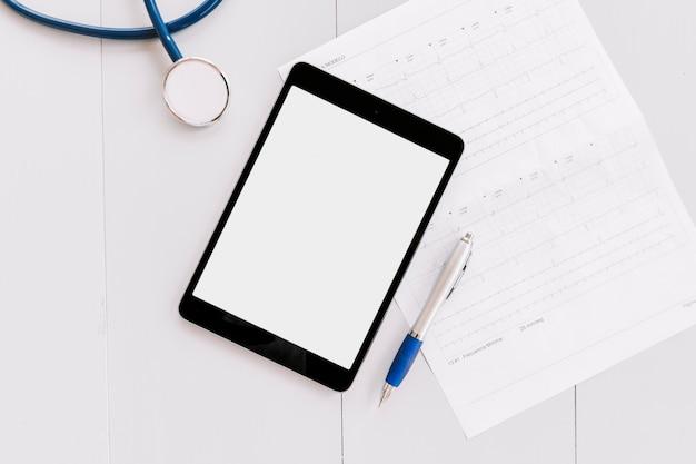 Stéthoscope; tablette numérique; graphique stylo et cardiogramme sur une surface en bois blanche Photo gratuit
