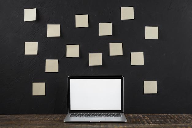 Sticky note stick sur un mur noir derrière l'ordinateur portable à écran blanc Photo gratuit