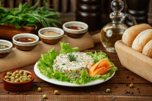 Stolichni de salade russe servi sur des feuilles de salade verte et une carotte décorative avec des haricots verts Photo gratuit