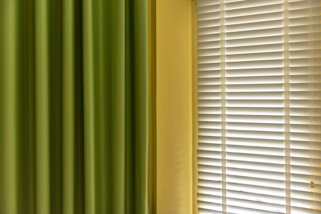 Stores vénitiens près de la fenêtre ou stores fenêtre et rideau vert, concept de décoration de fenêtre stores. Photo Premium