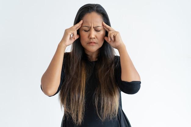 Stressée femme d'âge moyen touchant les temples et réfléchissant Photo gratuit