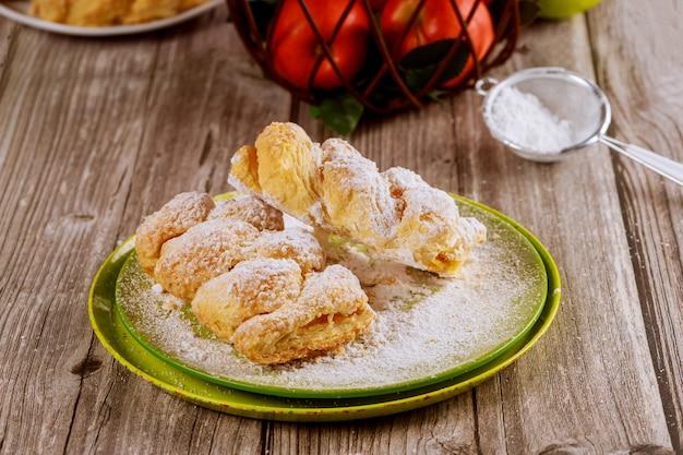 Strudel Aux Pommes En Poudre Sur Une Plaque Verte Avec Des Pommes Fraîches. Photo Premium