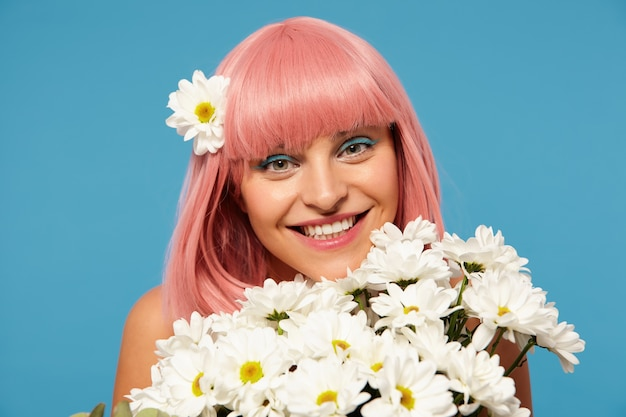 Studio Photo De Jeune Femme Aux Cheveux Rose Assez Romantique Avec Maquillage Festif Posant Dans Des Fleurs Blanches Sur Fond Bleu, Regardant Positivement La Caméra Avec Un Sourire Charmant Photo gratuit