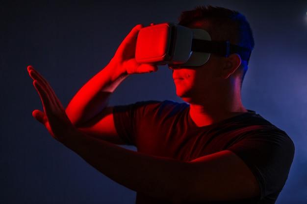 Stupéfié jeune homme casual chic portant la réalité virtuelle vr headset gesticulant mains Photo gratuit