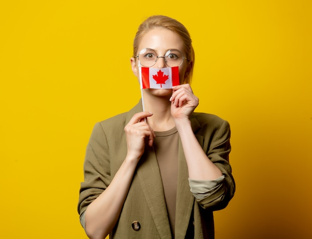 Style Femme Blonde En Veste Avec Drapeau Canadien Sur Jaune Photo Premium