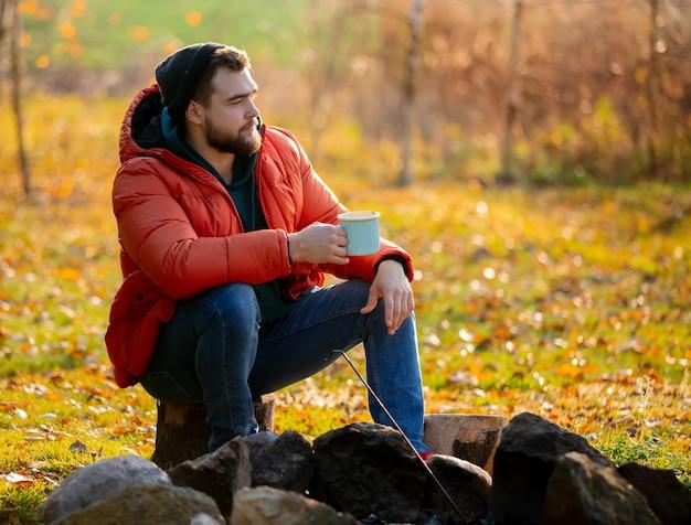 Style homme en doudoune avec une tasse de café assis près d'un feu de joie Photo Premium