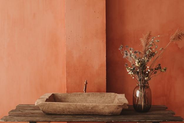 Style Intérieur Minimaliste. Fleurs Sèches Dans Un Vase En Verre Debout Sur Une étagère En Bois Avec Un évier Vintage à L'arrière-plan Du Mur Orange Photo Premium