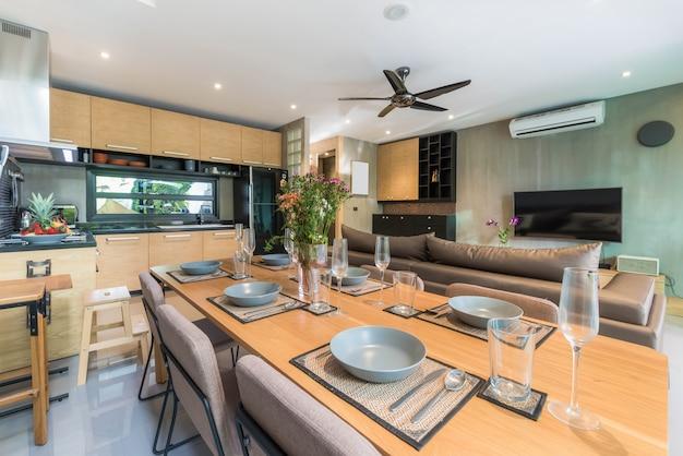 Style loft de design d'intérieur de luxe dans le coin cuisine avec comptoir en îlot et table à manger Photo Premium