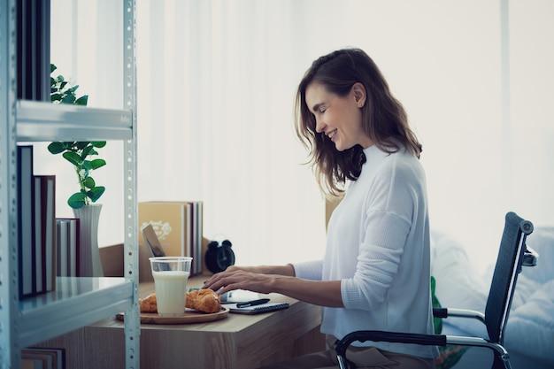 Style de vie femme travaillant en tapant sur un ordinateur portable dans une chambre élégante à la maison Photo Premium