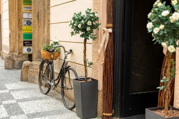 Style Vieille Europe, Un Vélo Avec Un Panier De Fleurs Fraîches Est Garé Près De L'entrée De La Maison Photo Premium