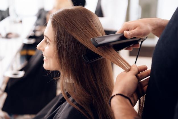 Le styliste est redresser les cheveux bruns de la femme. Photo Premium