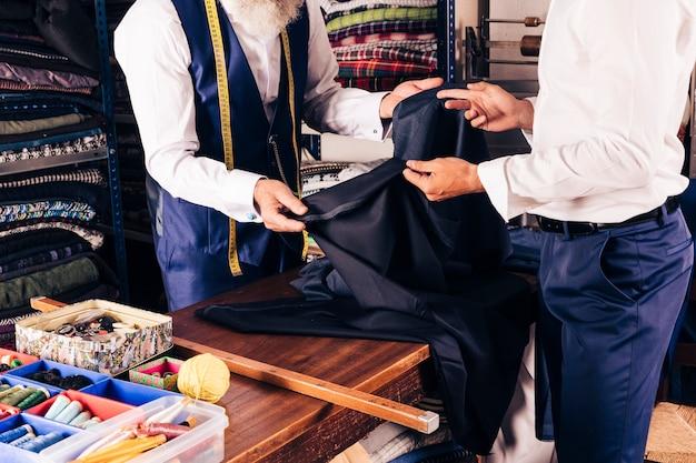 Styliste montrant le tissu à son client dans la boutique Photo gratuit