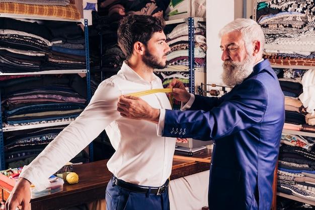 Styliste professionnel prenant la mesure de la poitrine de sa cliente Photo gratuit