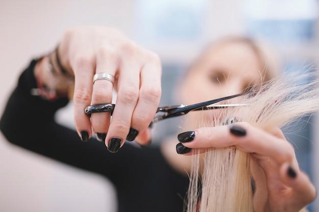 Styliste professionnel taillant les pointes de cheveux Photo gratuit