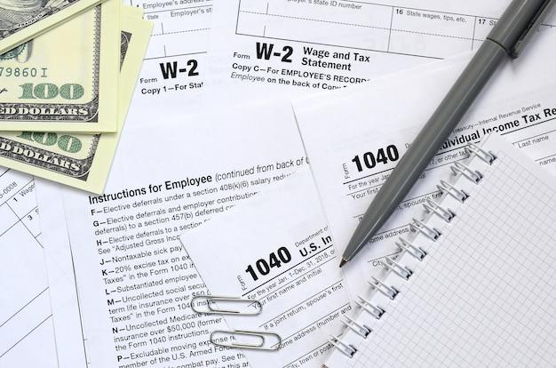 Le stylo, le cahier et les billets d'un dollar se trouvent sur le formulaire d'impôt 1040 us déclaration de revenus des particuliers Photo Premium