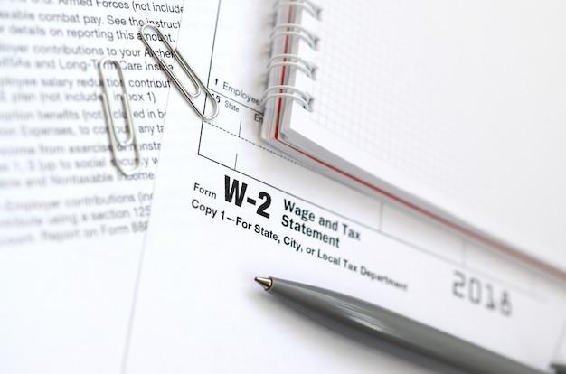 Le stylo et le cahier sur le formulaire d'impôt w-2 déclaration de salaire et d'impôt Photo Premium